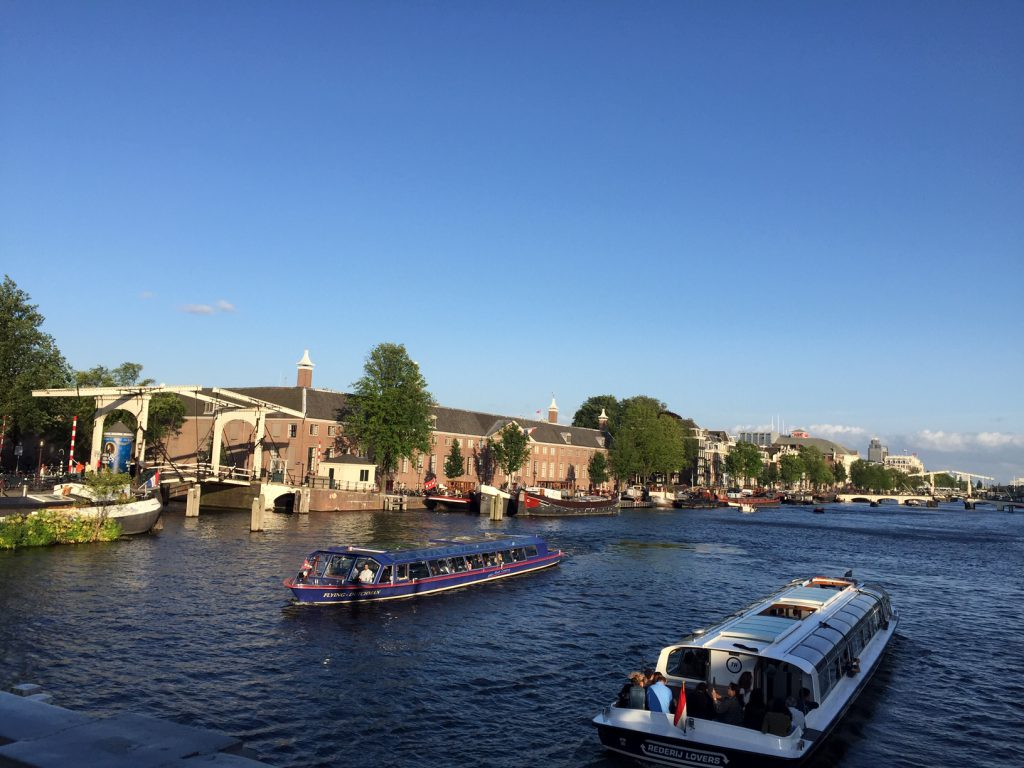 Rent a Bike in Amsterdam and go biking along river Amste to check the boats passing by.