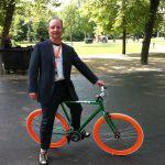Lex van Buuren zegt op een fiets met oranje velgen dat hij graag reisleider en lokale gids wil zijn tijdens het EK Voetbal 2020 in Amsterdam. Bijvoorbeeld voor Franstalige groepen.
