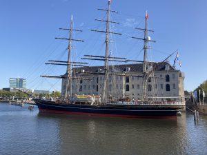 Fietstocht voor ouders met kinderen met lokale Amsterdamse gids - Foto met daarop Scheepvaartmuseum en met de Clipper Amsterdam ervoor
