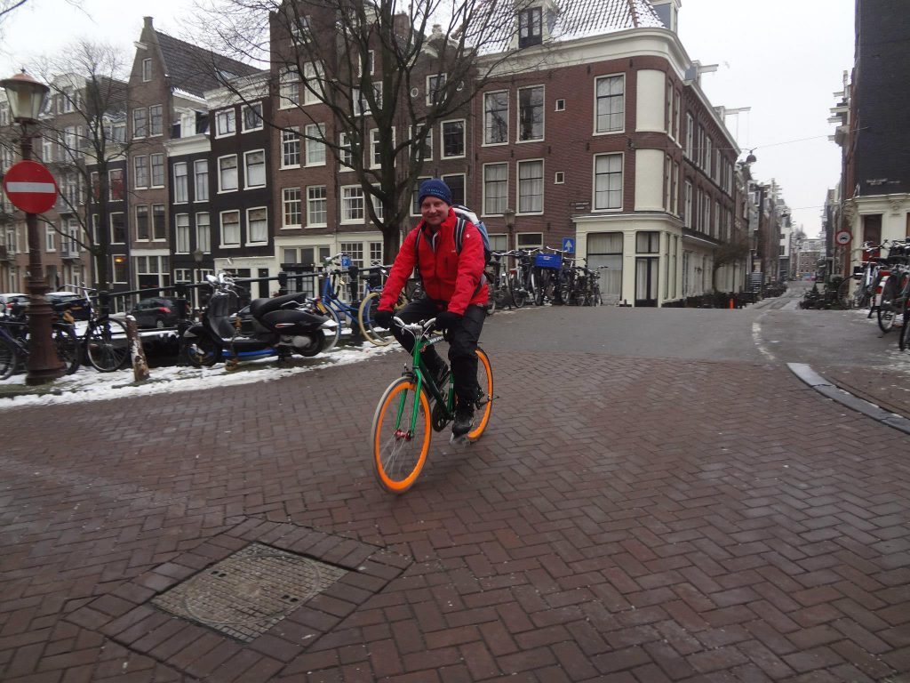 Bike guide Amsterdam Lex van Buuren from Lex and the City in winter time on his way to go ice skating on the canal Keizersgracht