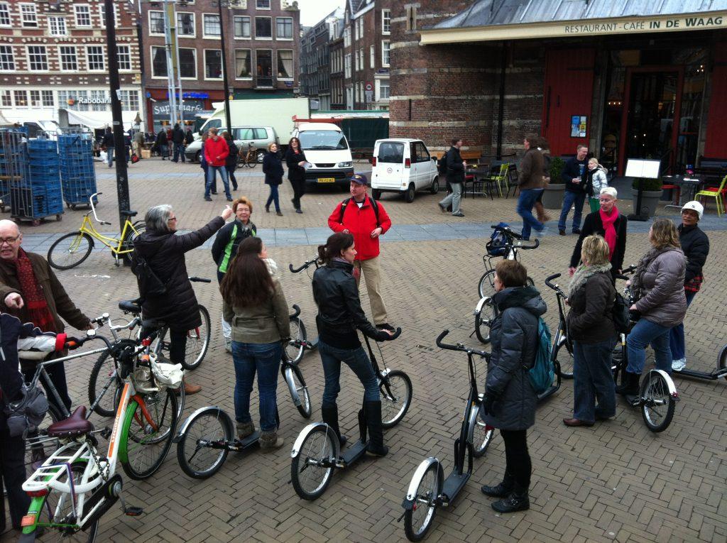 Stepgids Amsterdam van Lex and the City bij de Waag op de Nieuwmarkt met een groep medewerkers van het ziekenhuis
