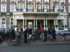 Eén van de stepgidsen van Lex and the City stopt met de groep voor het Amstel Hotel voor een anekdote tijdens deze ongebruikelijke Amsterdamse stadsrondleiding