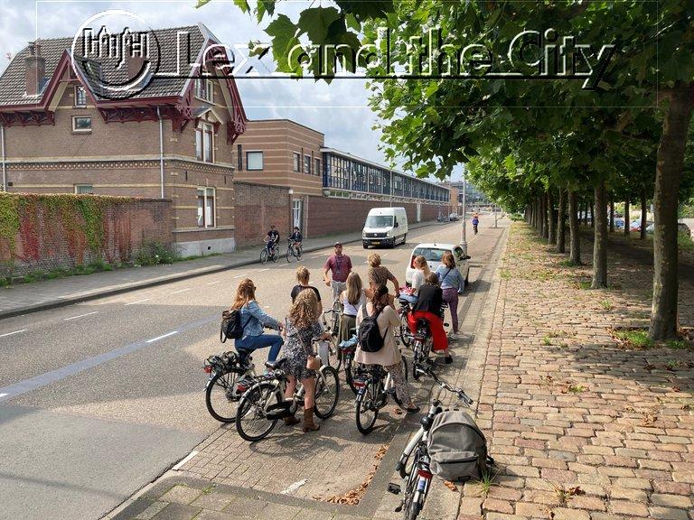 Fietstocht in ongewoon Amsterdam met lokale out of the box privé gids - Actief deel van een vrijgezellenfeest voor dames - Met Lex and the City Tour Lexperiences - Augustus 2021. Op foto de groep op de fiets tussen de voormalige Veemarkt en het z.g. kleinste Museum ter wereld in.